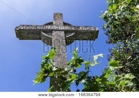 Old stone christian cross on a bright sunny day.