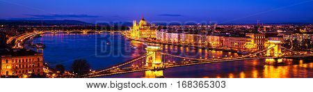 Budapest, Hungary. Chain bridge and Parliament building in Budapest, Hungary at sunset. Illuminated buildings and car traffic lights