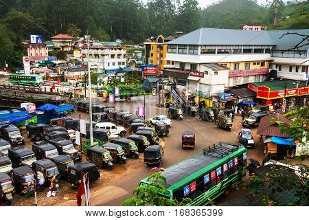 MUNNAR, INDIA - JUNE 24, 2016: Crowded junction in the mountain village Munnar located in Kerala, India. Tuk-tuk and buses traffic with people during the heavy rain