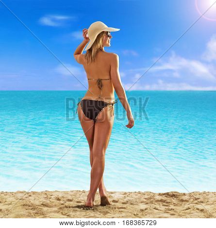 Feeling the sun at beautiful beach. sunbathing fitness woman looking the sea.