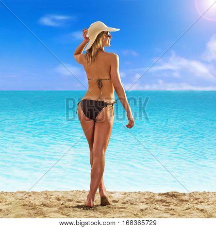 Feeling the sun at beautiful beach. sunbathing fitness woman looking the sea.