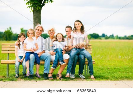 a big family are sitting on a bench in a park