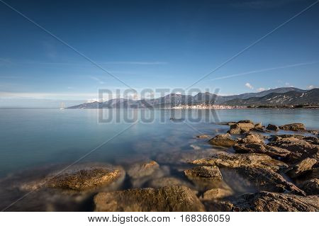 View across the bay of Saint Florent in Corsica with rocks in the foreground and a three mast sailing ship in the harbour with the mountains of Cap Corse behind the town of Saint Florent