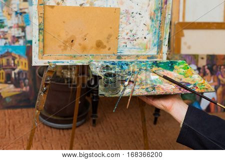 Artist hand holding palette with mixed pigment and paintbrushes ready to paint on canvas.