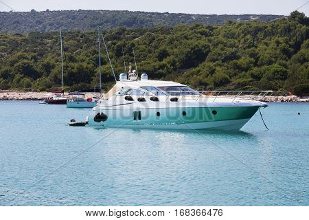 Luxury yacht in azure seas parked in a beautiful blue bay. Modern white Yacht in the sea around island on Croatia.