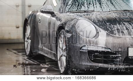 Washing a luxury sport car in the suds, close up