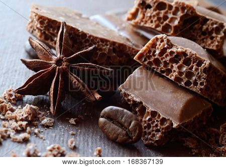 Black porous chocolate in bars with anise and coffee beansfood background with horizontal composition
