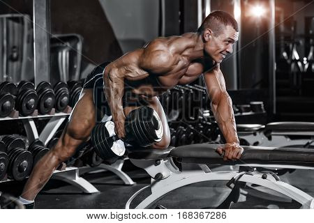 Athlete muscular bodybuilder training hands with dumbbells in gym