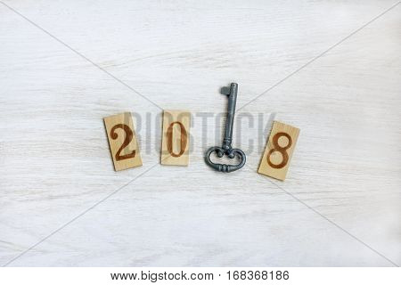 lay flat wooden figures and a top view of an iron key / important year number 2018