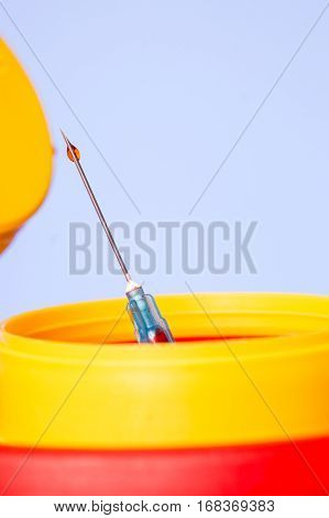 Yellow medical needle disposal waste container syringe needle with red drop on the tip. Isolated