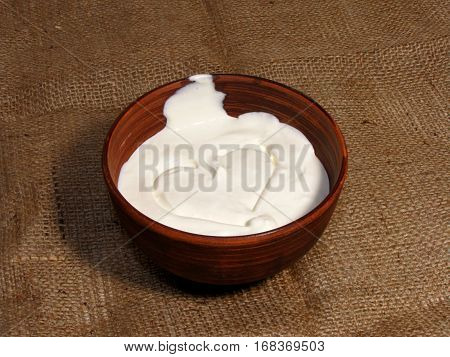 Romantic breakfast with painted heart on Valentine's Day on jute background. Sour cream served in handmade old pottery. Top cream is drawn heart.