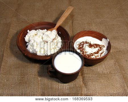 Romantic breakfast with painted heart on Valentine's Day on jute background. Milk cottage cheese and sour cream served in handmade old pottery. Heart is drawn from chocolate.