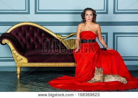 Woman in red dress sits on couch, lynx cub lies on dress hem on floor.
