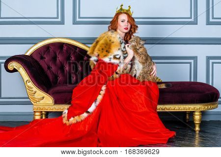 Red-haired woman in red dress, cloak and with crown on head sits on couch holding lynx cub.