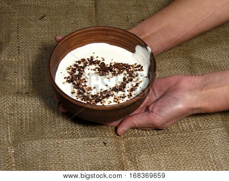 Romantic breakfast with painted heart on Valentine's Day on jute background. Sour cream served in handmade old pottery. Heart is drawn from chocolate. Bowl holding with hands.