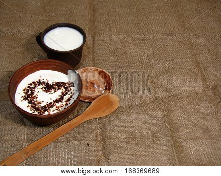Romantic breakfast with painted heart on Valentine's Day on jute background. Milk and sour cream served in handmade old pottery. Heart is drawn from chocolate. Copy space.