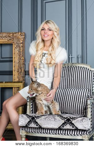 Young blonde woman sits on armrest of armchair on which lynx cub sits.