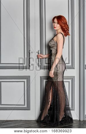 Red-haired young woman in white and black suit stands in room, holding door handle.