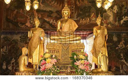 BANGKOK, THAILAND - JANUARY 2: Details of golden buddha statue with tales of the lord Buddha's former births behind at Wat Nairong