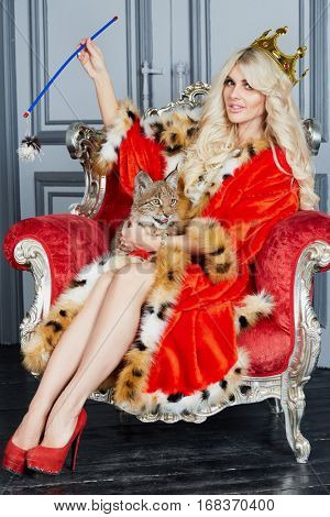 Young blonde woman in red cloak and crown sits in armchair with lynx cub.