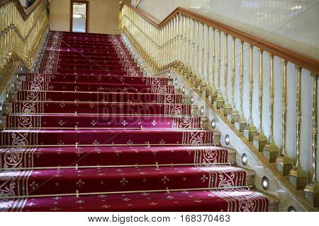 Stairs with handrails covered with red carpet.