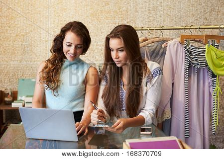 Two women working in a clothes shop using a laptop computer