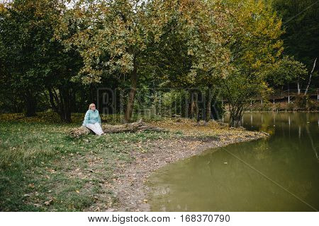 sad alone senior woman sitting on a log by the lake outdoor in the park. loneliness concept