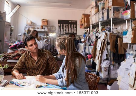 Male manager training apprentice at a clothing design studio