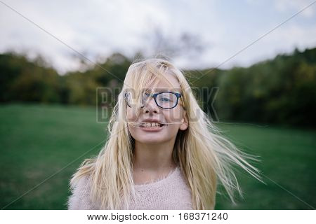 portrait of smiling disheveled blonde girl with glasses outdoors in park