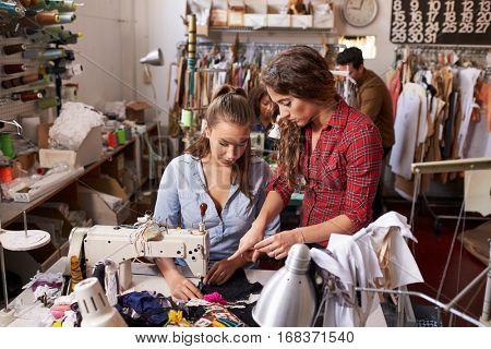 Colleague advises trainee machinist at clothes design studio