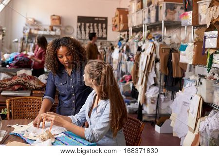 Woman stands training an apprentice at clothes design studio