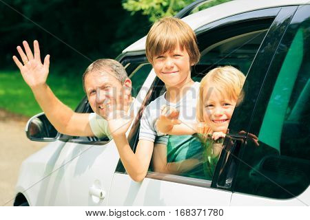 family sitting in their car, leaving for holidays