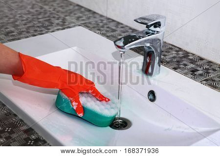 hand of woman in glove who washes white sink