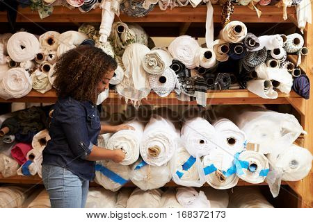 Mixed race woman selects fabric at a clothing design studio