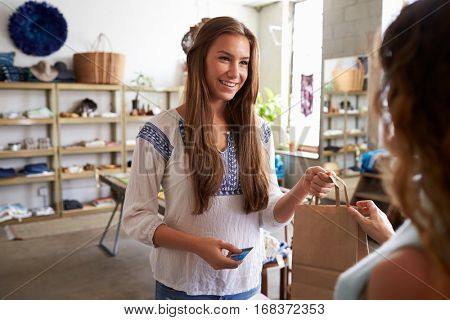 Young female customer takes bag from assistant in a boutique