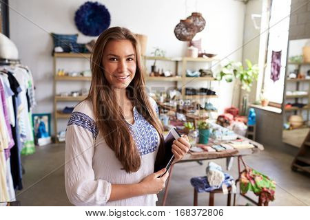 Teenage boutique assistant holding tablet computer in shop