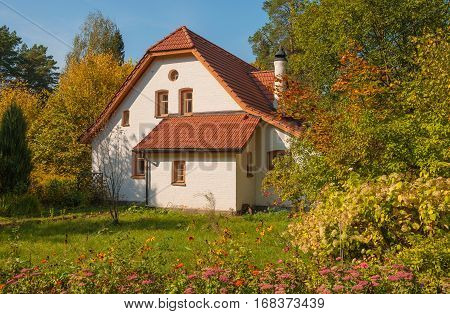 The small white house with a slate roof in the autumn park
