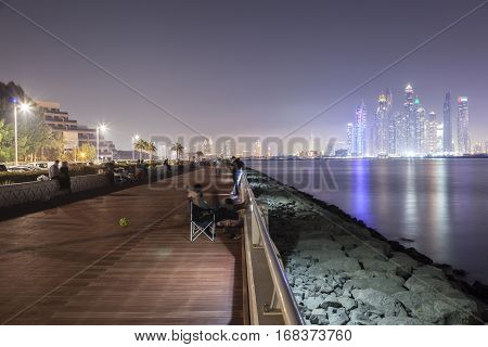 DUBAI UAE - DEC 2 2016: Promenade at the Palm Jumeirah with Dubai Marina Skyline in the background. United Arab Emirates Middle East