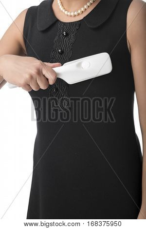 Woman using a lint brush to remove debris from her dress isolated on white background.