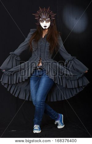 actress brunette girl with a theatrical mask on a dark background