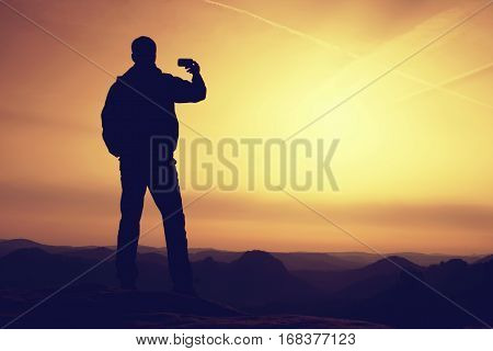 Hiker Hold In Hand Phone And Take Photo Of Misty Landscape.