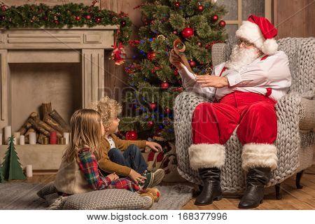 Santa Claus reading wishlist while children sitting on carpet
