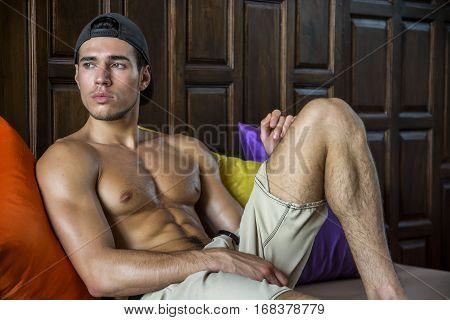 Shirtless athlete lying on the pillows and looking away. Horizontal indoors shot.