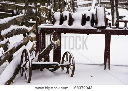 Old rusty farm equipment covered with snow at winter, mountain Kozomor, Serbia
