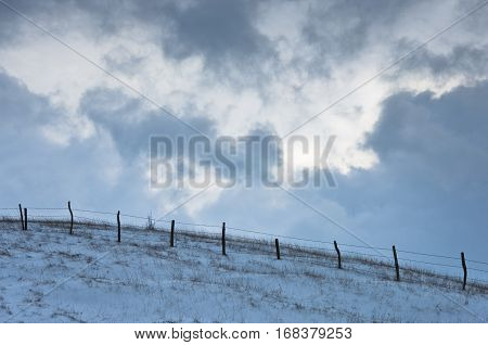 Hill with a fence covered with snow under dramatic clouds at winter, mountain Kozomor, Serbia
