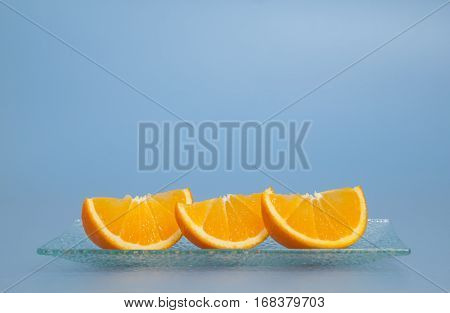 Three pieces of fresh oranges on a plate blue background