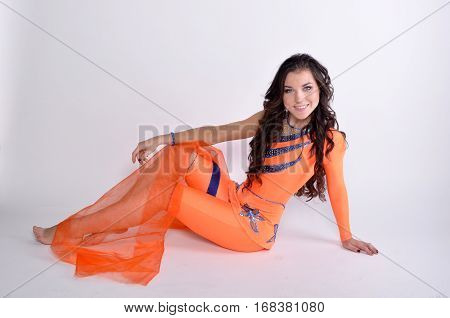 Beautiful girl athlete sitting and smiling in an orange suit