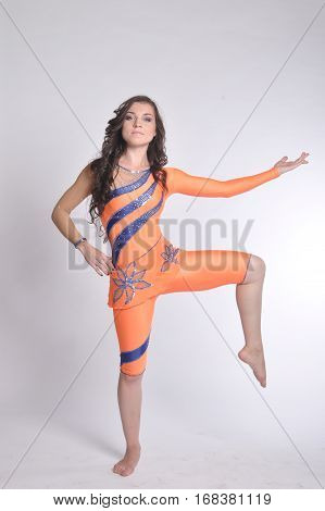 Young athletic girl in an orange suit Lycra