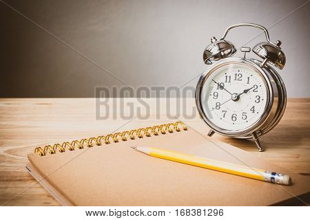 Concept time management Clock and notepad with pencil on table