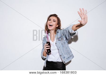 Photo of a young cheerful lady dressed in jeans jacket standing isolated over white background while drinking aerated sweet water.